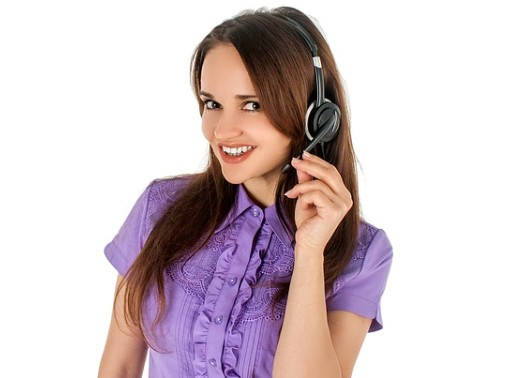 Stock Photo Image of person holding the microphone part of a phone headset while smiling at the camera.
