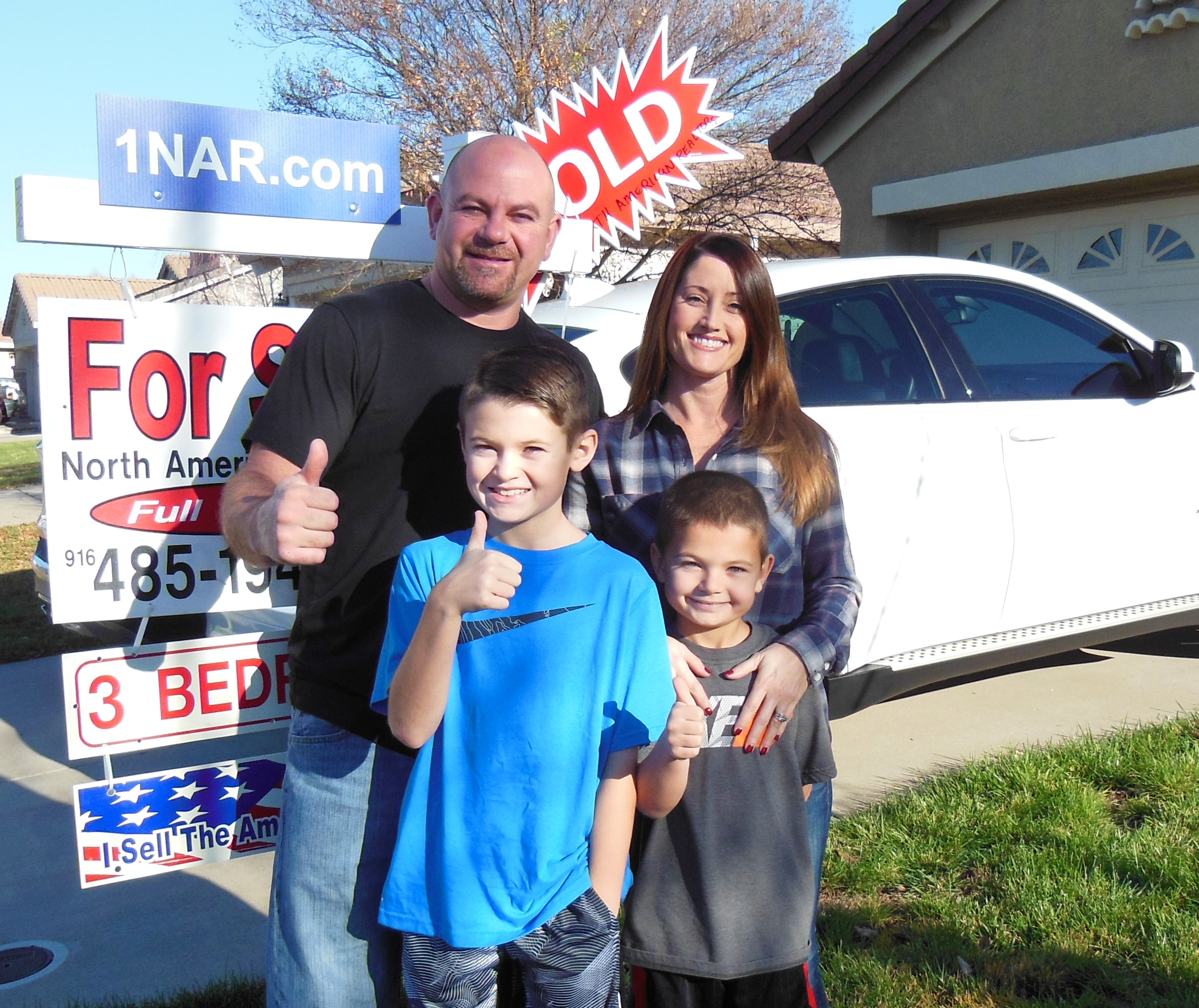 Photo of our clients with their SOLD sign.